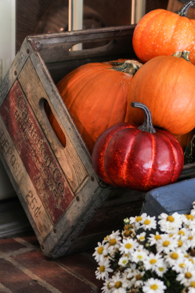 An old carnation milk crate hold pumpkins on the porch
