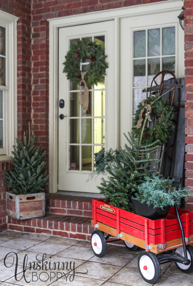 Evergreen trees in a red wagon and sled on a Christmas porch