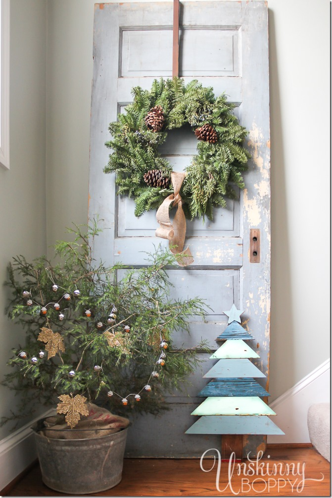 Gorgeous rustic Christmas decor. Tree in a galvanized bucket, chippy old door with a wreath, and a Christmas tree made from architectural salvaged wood.