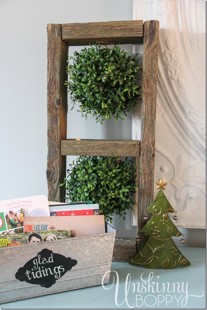 """Boxwood kissing balls and """"Glad Tidings"""" label on a galvanized bucket for Christmas cards"""