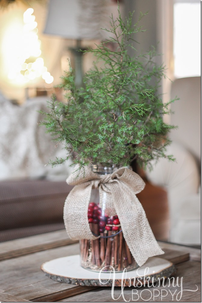 Simple holiday table centerpiece- evergreen in a glass vase filled with cinnamon sticks and cranberries tied with a burlap bow.