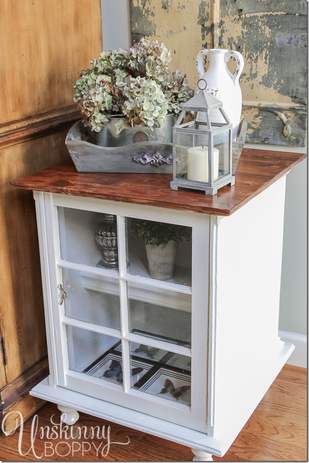 This end table is decorated with rustic pieces that reflect a farmhouse style, like the flowers in these vintage steel watering cans, the white ceramic vase, and a gilded metal lantern.