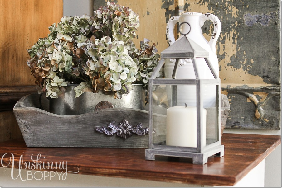 A closer look at the vintage and rustic table decorations. The metal candle lantern and metal watering cans holding flowers give this end table a uniquely farmhouse style.