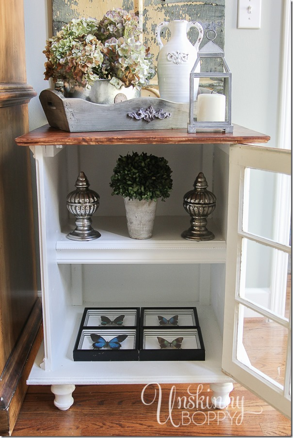 This end table  has a cabinet with shelves that are perfect for adding more decorative pieces to your end table design. Love the four butterflies on the bottom shelf!