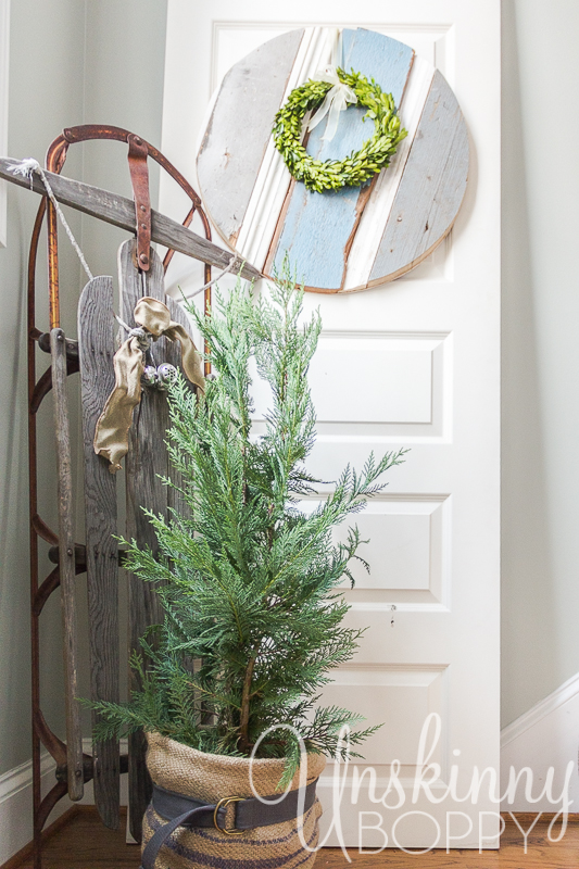 Old Sled with belted burlap tree and Christmas wreath.