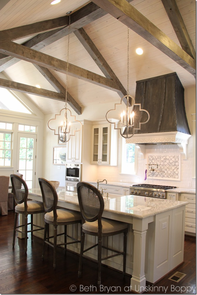 Incredible Kitchen with rustic ceiling beam and french style hood over range