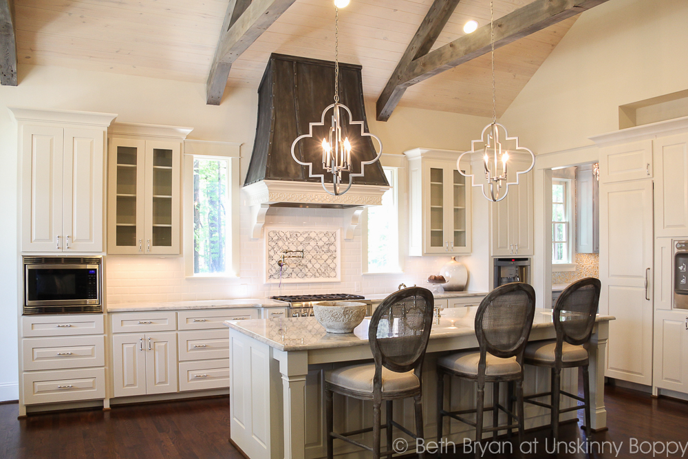 French country kitchen with ceiling beams and wooden vent hood