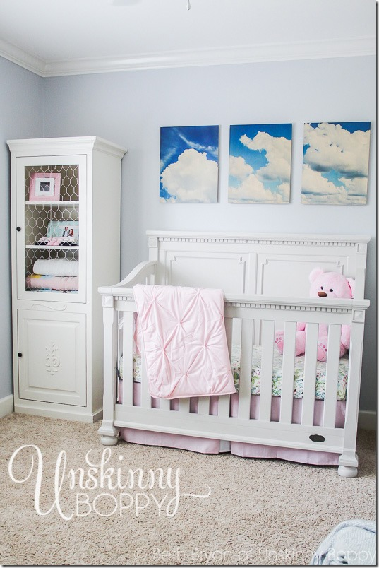 Simple nursery with cloud photos above crib