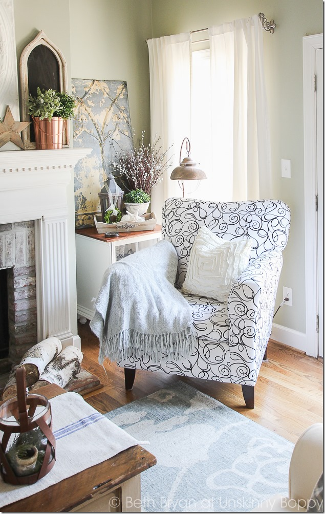 Love the swirly black and white fabric on that side chair.  The copper lighting and mantel decor, the pressed tin piece- love