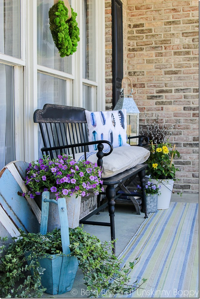 Black metal Front porch bench with watercolor feather pillow, french grain sack cushion and flowers in a bucket for Spring | Cozy Spring Home Tour | www.unskinnyboppy.com
