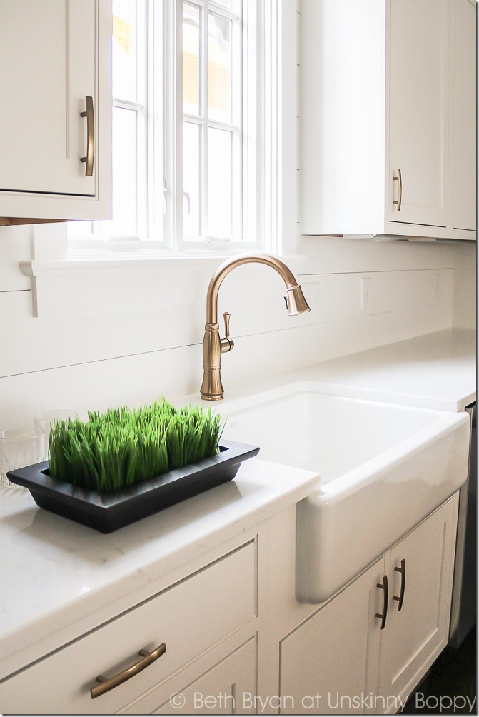 aged bronze kitchen faucet in white kitchen with shiplap