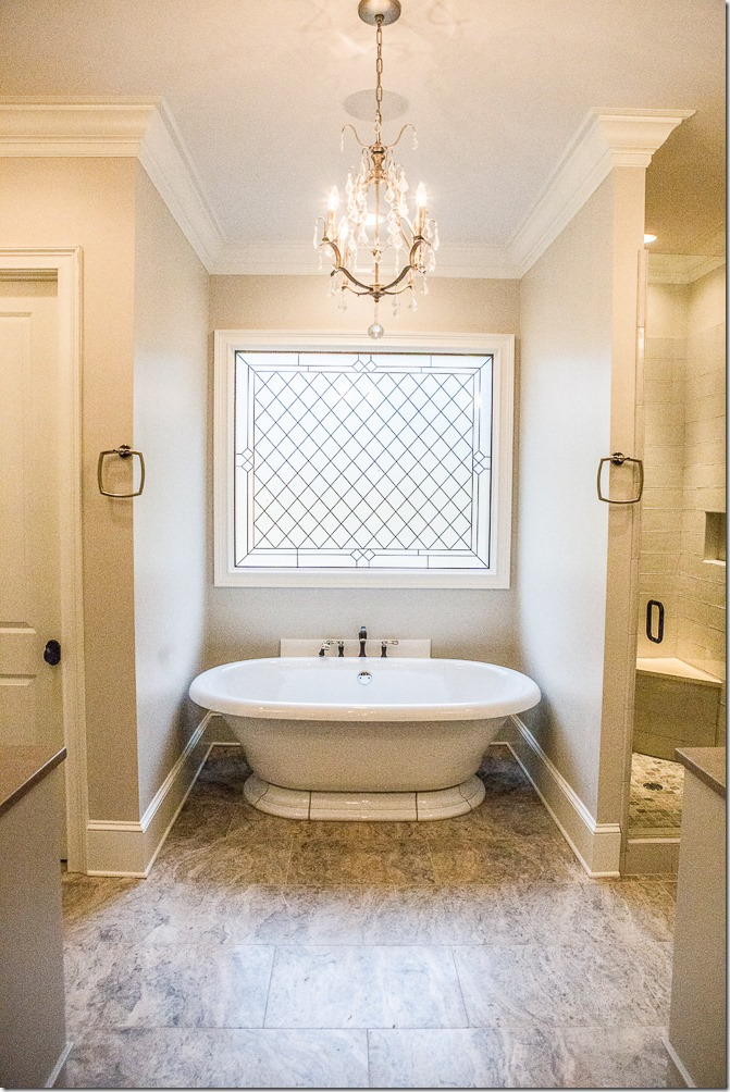freestanding bathroom tub with leaded glass window and chandelier