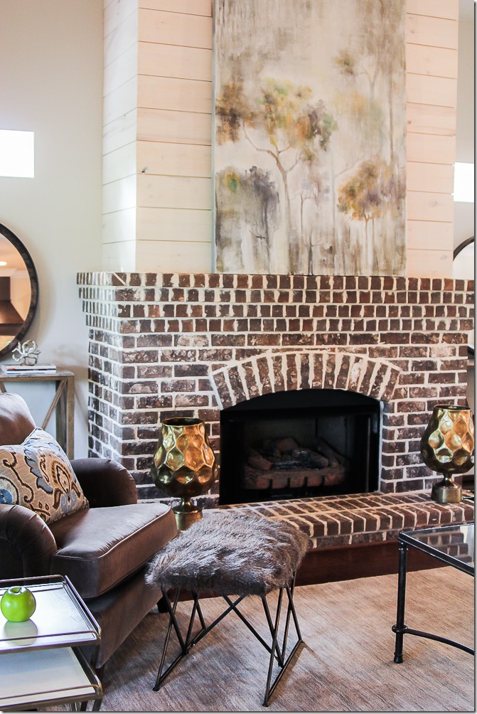 Who else loves the look of this traditional arched brick fireplace with shiplap above? #imafan #fireplacelove #fireplacedecor