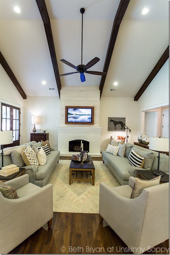 ceiling beams in living room with shiplap fireplace