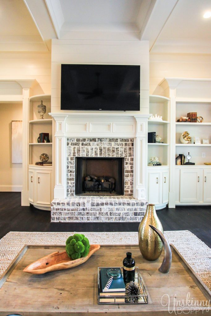 Rounded built-ins beside fireplace with coffered ceiling