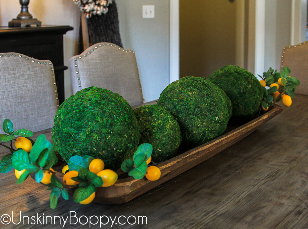 Moss balls and lemon stems in a dough bowl on dining table centerpiece
