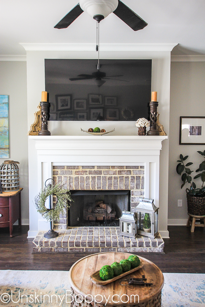 Springtime wreath and lanterns on a brick fireplace