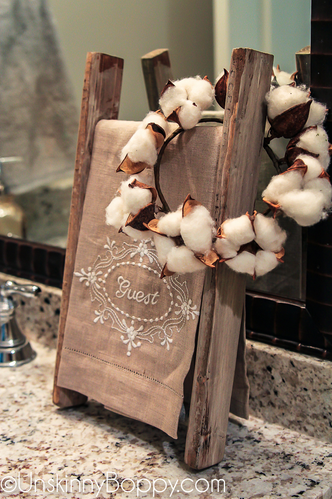 small cotton wreath on a guest towel ladder in bathroom