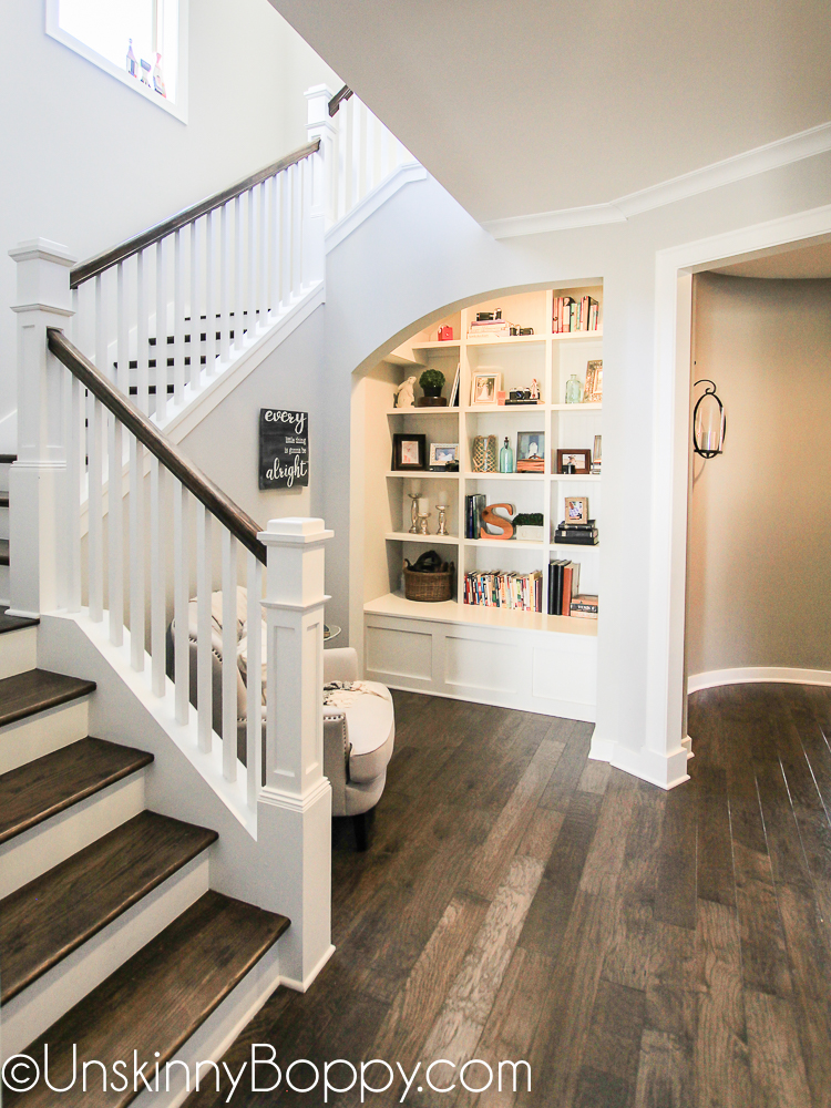 Grand staircase with built-in bookcase nook and circular hallway