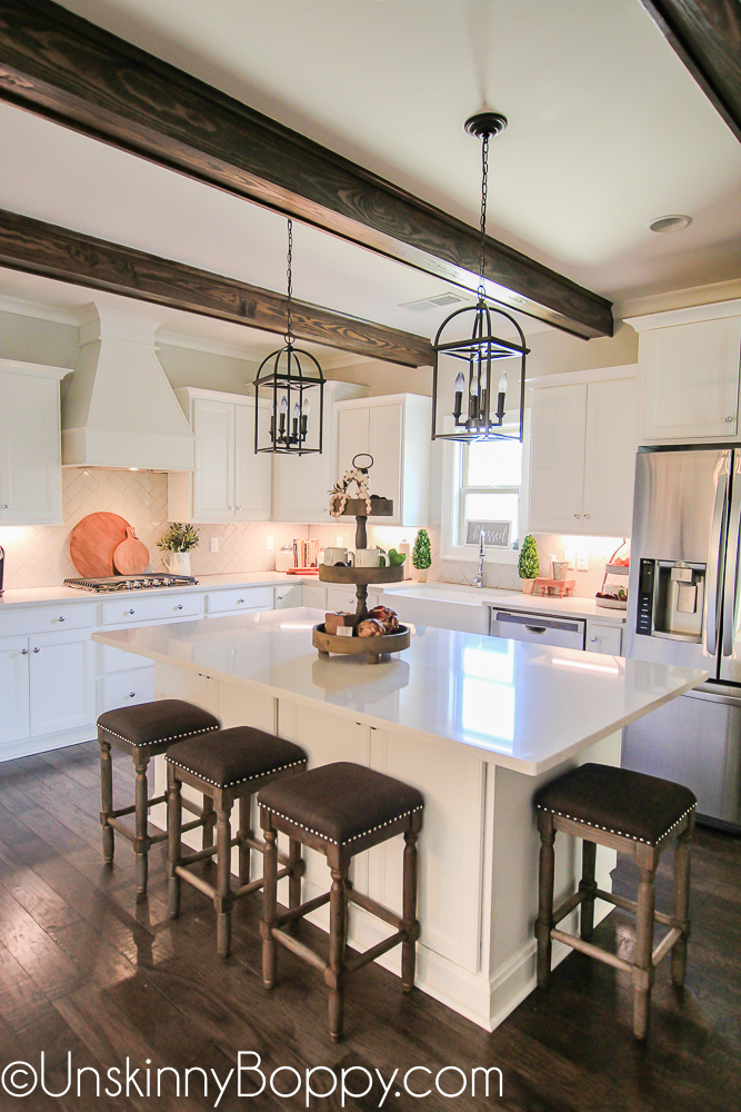 White kitchen cabinets with wooden beams