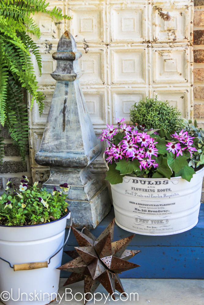 Front Porch Decor Ideas- flowers in white buckets, moravian star and garden finial