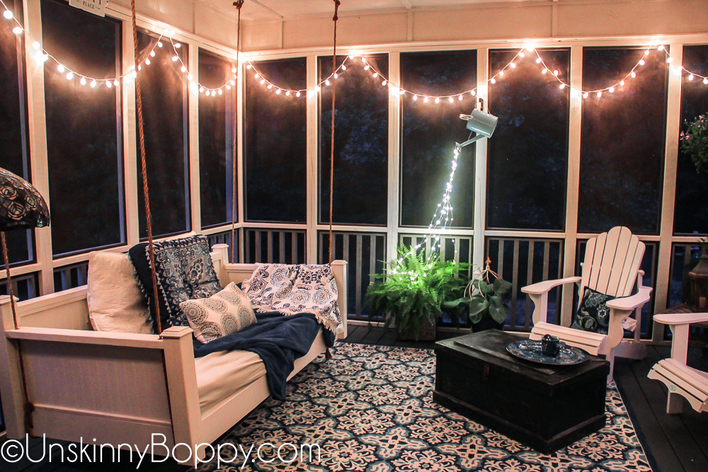 Cozy back porch with strings of lights and bed swing