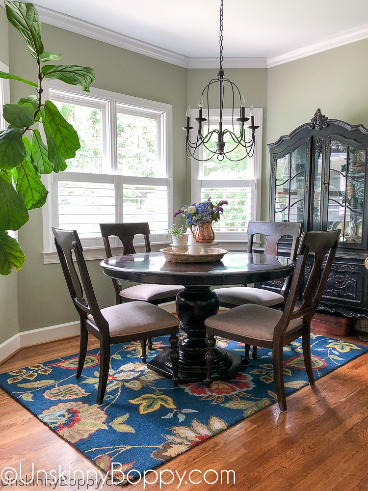 Kitchen table with dark blue floral rug and copper accents