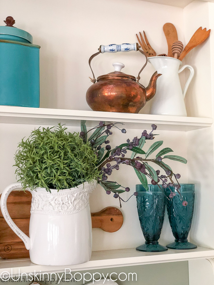 Decorating shelves above kitchen sink with copper and blues