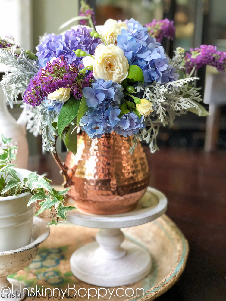 Periwinkle Hydrangea and white rose bouquet in a copper pitcher