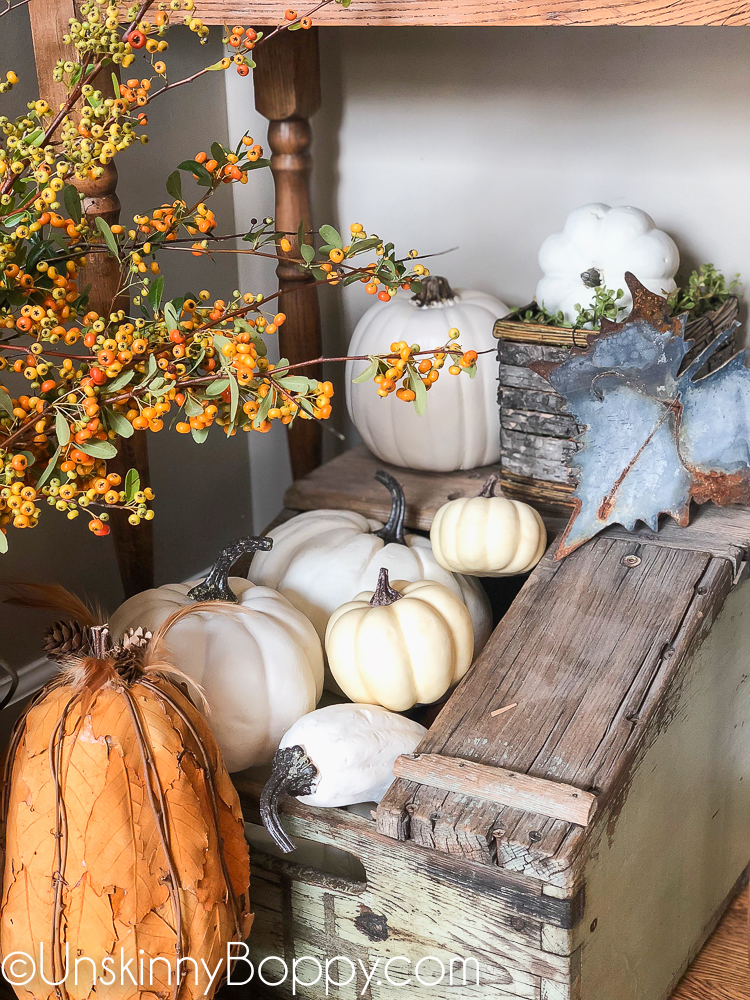 white pumpkins in a green box with pyracantha berries