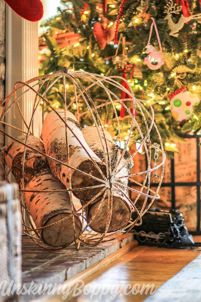 Birch logs in wire sphere beside Christmas tree