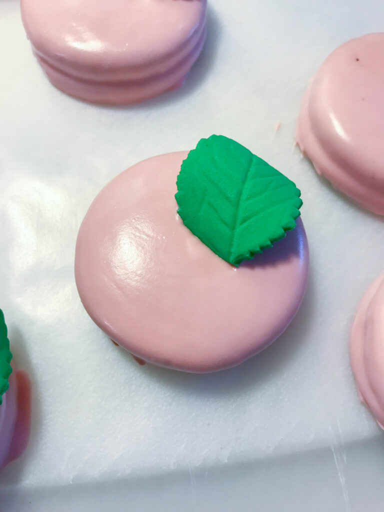 adding leaf onto oreo for bridal shower dessert