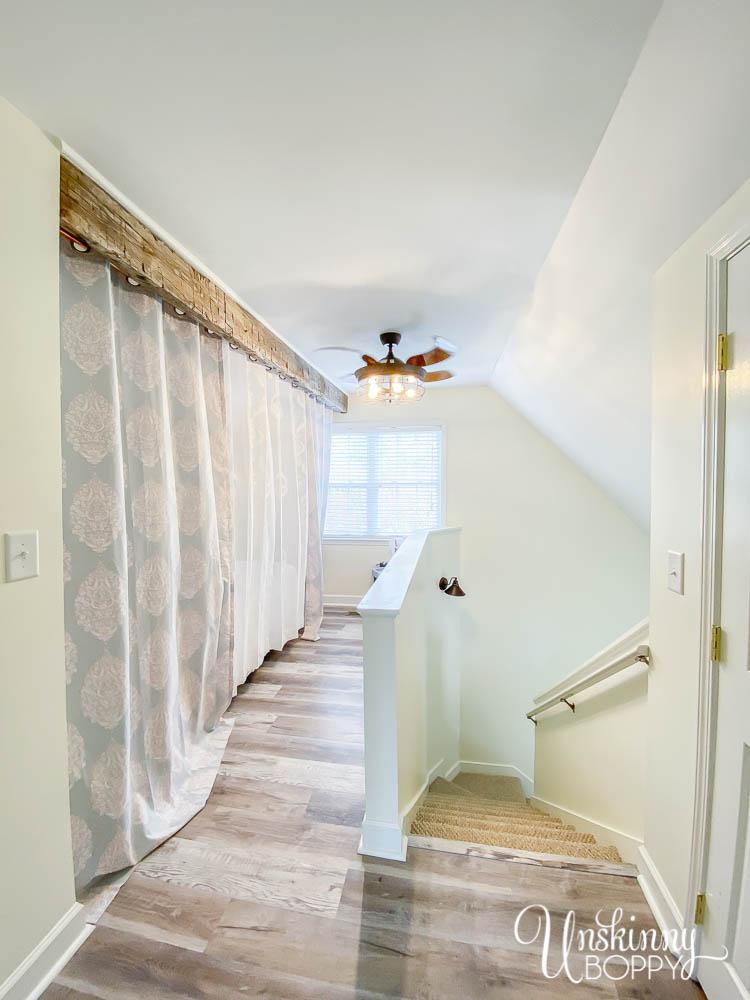 Curtains on loft behind hand-hewn beam