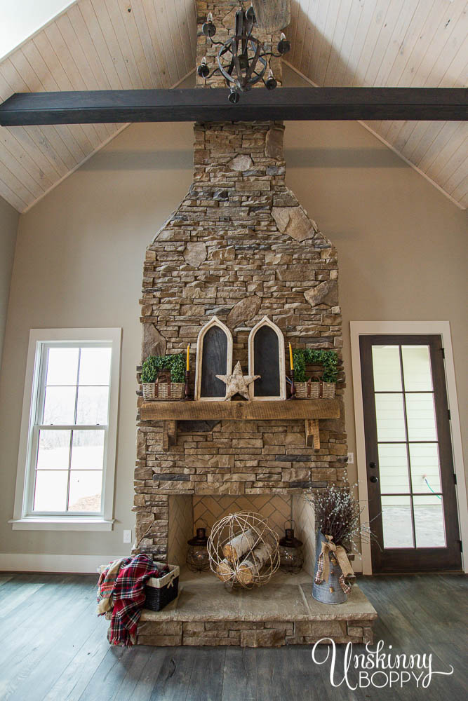 two-story fireplace with stacked stone and rustic mantel
