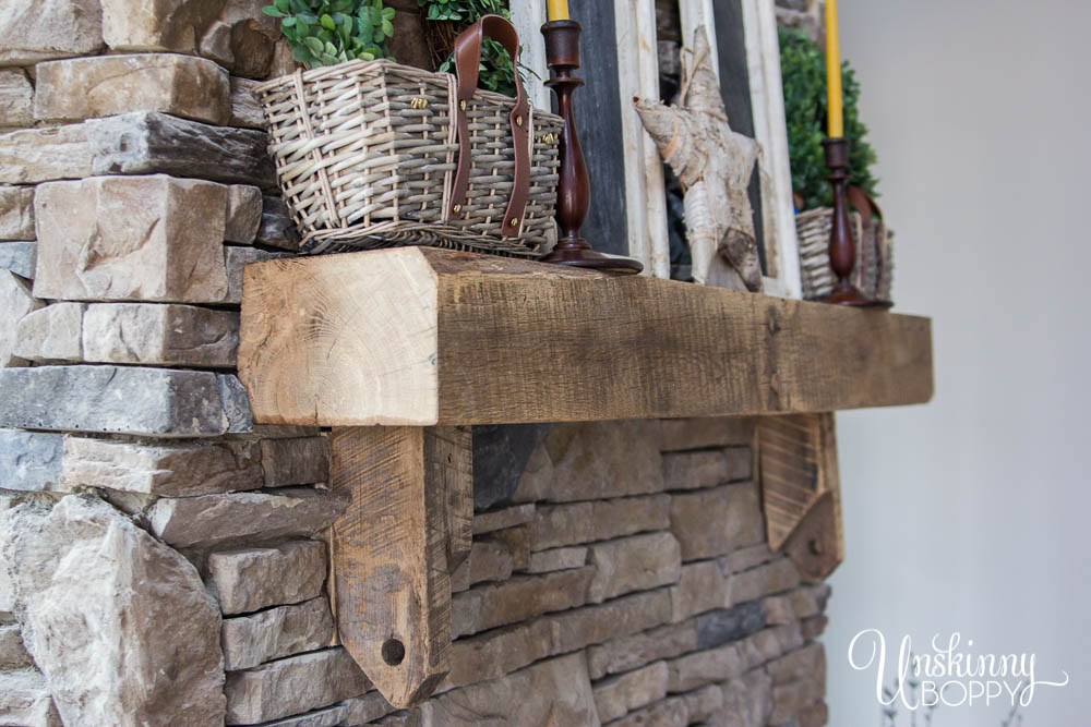 Hand-hewn mantel on rock fireplace